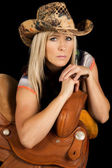 Cowgirl leaning on saddle