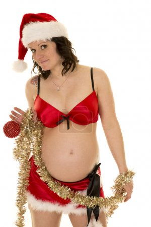 Photo for A pregnant woman in her Santa costume with tinsel wrapped around her, with her tattoo showing. - Royalty Free Image