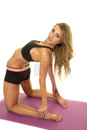A fit woman laying back stretching with a serious ...