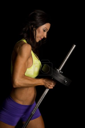 Woman with barbell on black