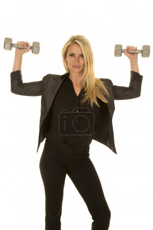 Photo for A businesswoman in her business clothes, working out with weights. - Royalty Free Image