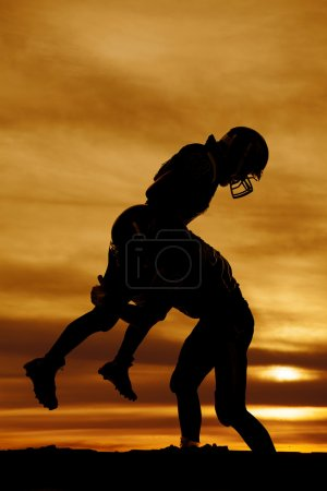 Photo for A football player making a hard hit on another player. - Royalty Free Image