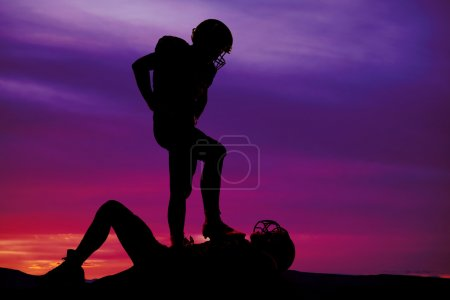 Silhouette of two football players