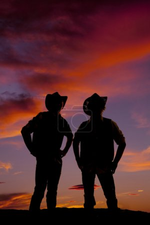 silhouette of two cowboys at sunset