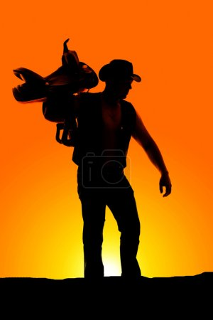 Silhouette of cowboy with saddle