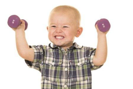 little boy holding dumbbells
