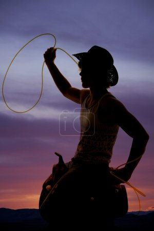 silhouete of a cowboy on a saddle with a rope