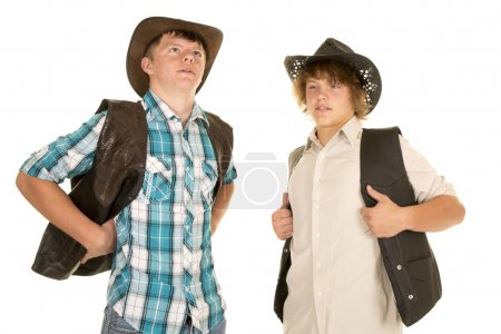 two young cowboys hold back vests