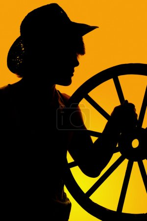 silhouette of cowboy holding wheel