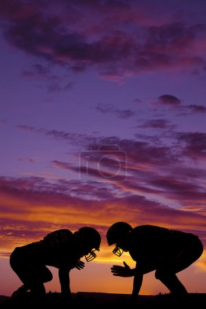 Photo for A silhouette of two football players getting ready to hit outdoors - Royalty Free Image
