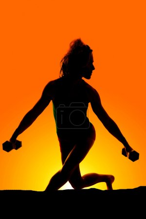 silhouette of woman with weights