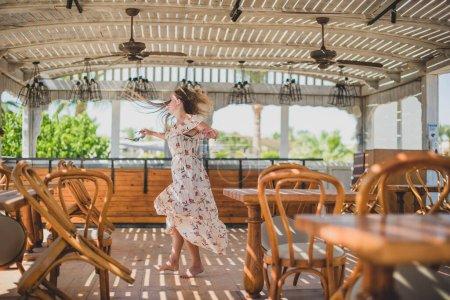 Photo pour Fille dansant dans un café sur la plage. jeune belle femme mince sur la plage du coucher du soleil, ludique, danse, course à pied, tenue bohème, style indépendant, vacances d'été, ensoleillé, s'amuser, humeur positive, romantique - image libre de droit
