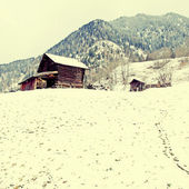 Old wooden barn in the Alps mountains at winter