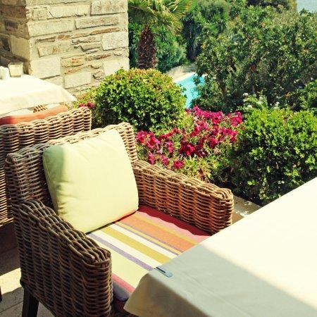 Wicker armchair on terrace overlooking the sea and garden (Greec