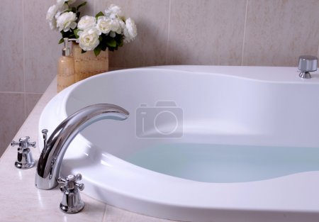 White bath tub with faucet and mosaic tiles