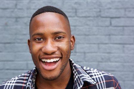 Photo pour Portrait d'un jeune Africain souriant debout contre un mur gris - image libre de droit