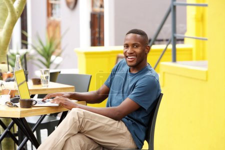 Smiling guy sitting at a cafe with a laptop