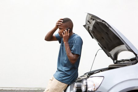 Photo for Young African man having trouble with his broken car calling for help on cell phone - Royalty Free Image