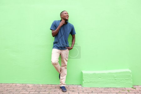 Photo for Full length portrait of stylish young african man standing against a green wall and looking away - Royalty Free Image