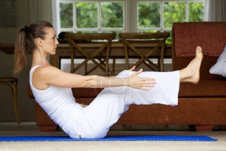 Yoga woman exercising by lifting legs