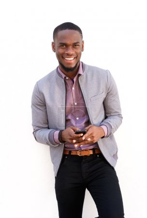 Photo for Portrait of a smiling young african man standing with a mobile phone - Royalty Free Image