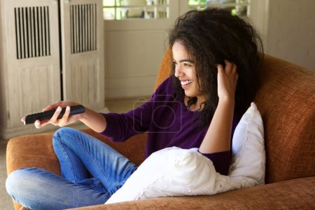 Woman with remote control watching tv
