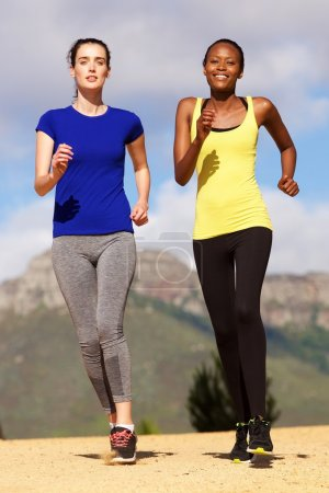 Photo for Full body portrait of two female friends running outdoors in nature - Royalty Free Image