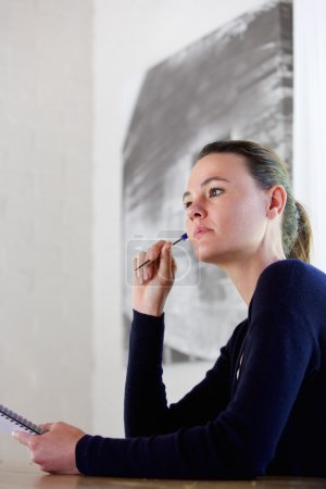 Thoughtful young woman with pen