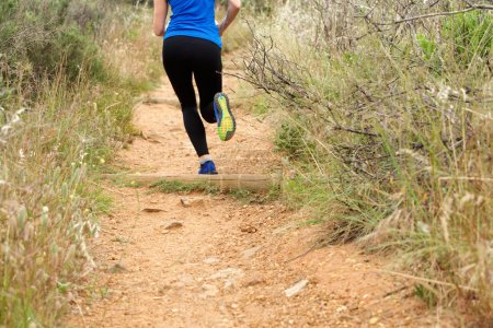 Back of woman running on dirt path