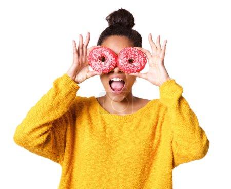 Photo pour Gros plan portrait de jeune femme africaine excitée couvrant ses yeux de beignets sur fond blanc - image libre de droit