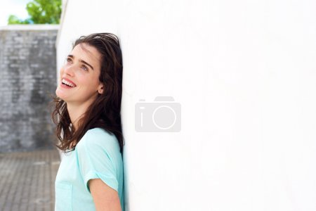 Smiling woman leaning against white wall looking up