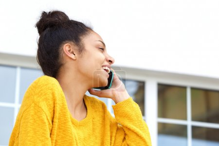 African woman talking on cell phone and smiling
