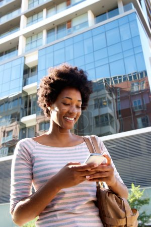 Smiling woman walking with mobile phone