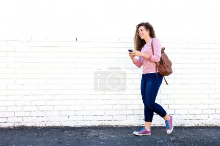 Smiling teen girl walking with cellphone