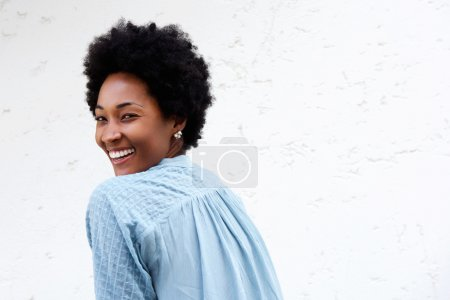 Photo for Rear view portrait of young african lady looking over shoulder and smiling against white background - Royalty Free Image