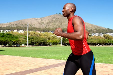 Photo for Side portrait of fit young african guy running outside at the park - Royalty Free Image