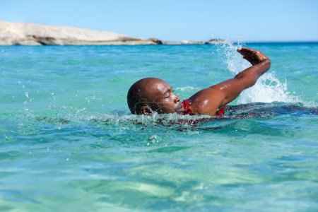 Young african man swimming in sea