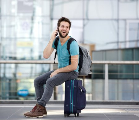 Photo for Portrait of a happy young man calling by mobile phone at airport - Royalty Free Image