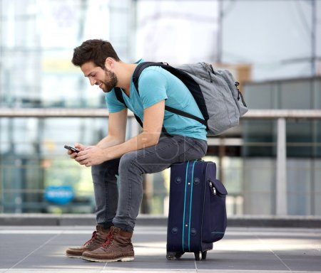 Traveler sitting sending text message