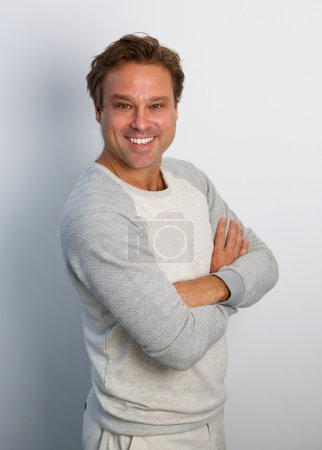 Friendly man smiling with arms crossed
