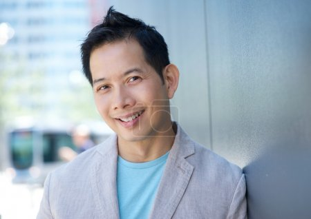 Charming asian man smiling outdoors