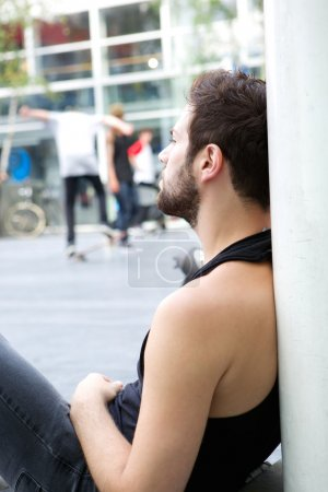 Young man with beard sitting outdoors