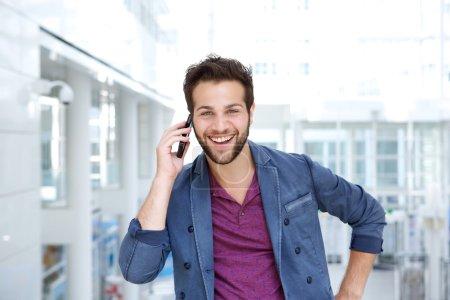 Photo pour Portrait d'un mec cool souriant avec téléphone portable - image libre de droit