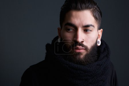 Photo for Close up portrait of a edgy modern young man with beard and piercings posing on gray background - Royalty Free Image