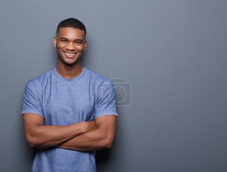 Photo for Portrait of a smiling black man posing with arms crossed on gray background - Royalty Free Image