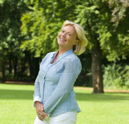 Photo for Portrait of a middle aged woman smiling outdoors - Royalty Free Image