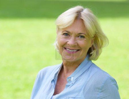 Photo pour Gros plan portrait d'une femme plus âgée souriant à l'extérieur - image libre de droit