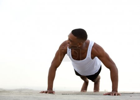 Young athletic man smiling and doing push ups