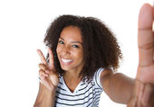 Happy young woman showing peace sign in selfie