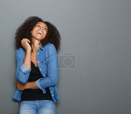 Young african american woman laughing on gray background